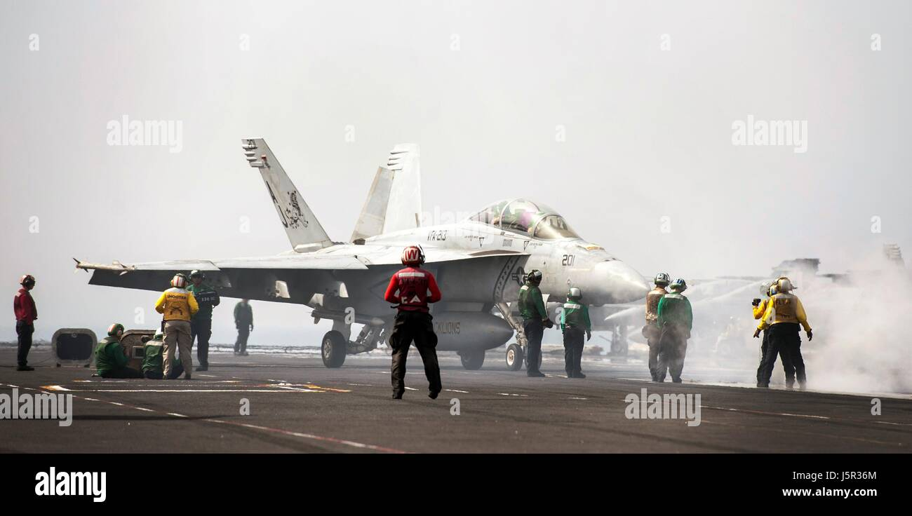 A USN F/A-18F Super Hornet jet fighter aircraft lands on the flight deck aboard the USN Nimitz-class aircraft carrier - Stock Image