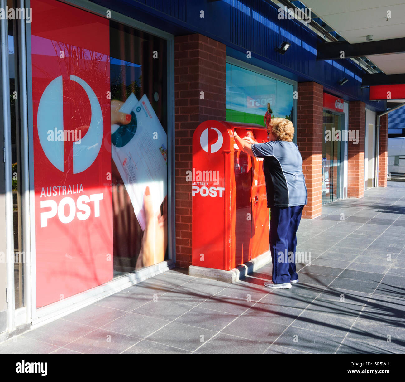 Mature Woman posting a letter in an Australia Post letterbox, Shellharbour, New South Wales, NSW, Australia - Stock Image