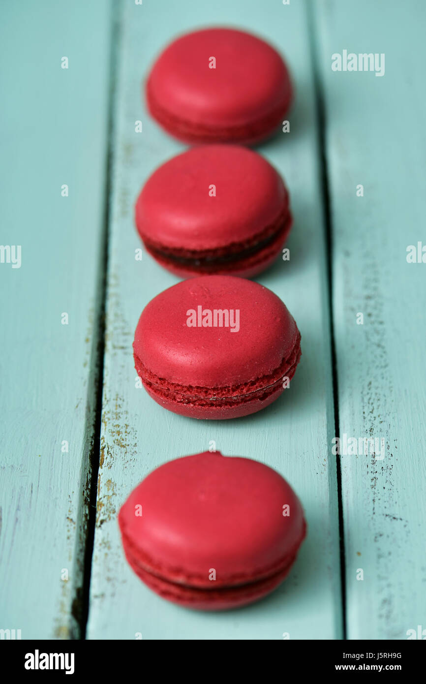 some appetizing red macarons put in line on a pale green rustic wooden table - Stock Image