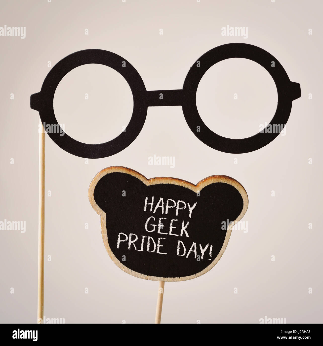 a pair of round-framed eyeglasses attached to a wooden handle and the text happy geek pride written in a black signboard, - Stock Image