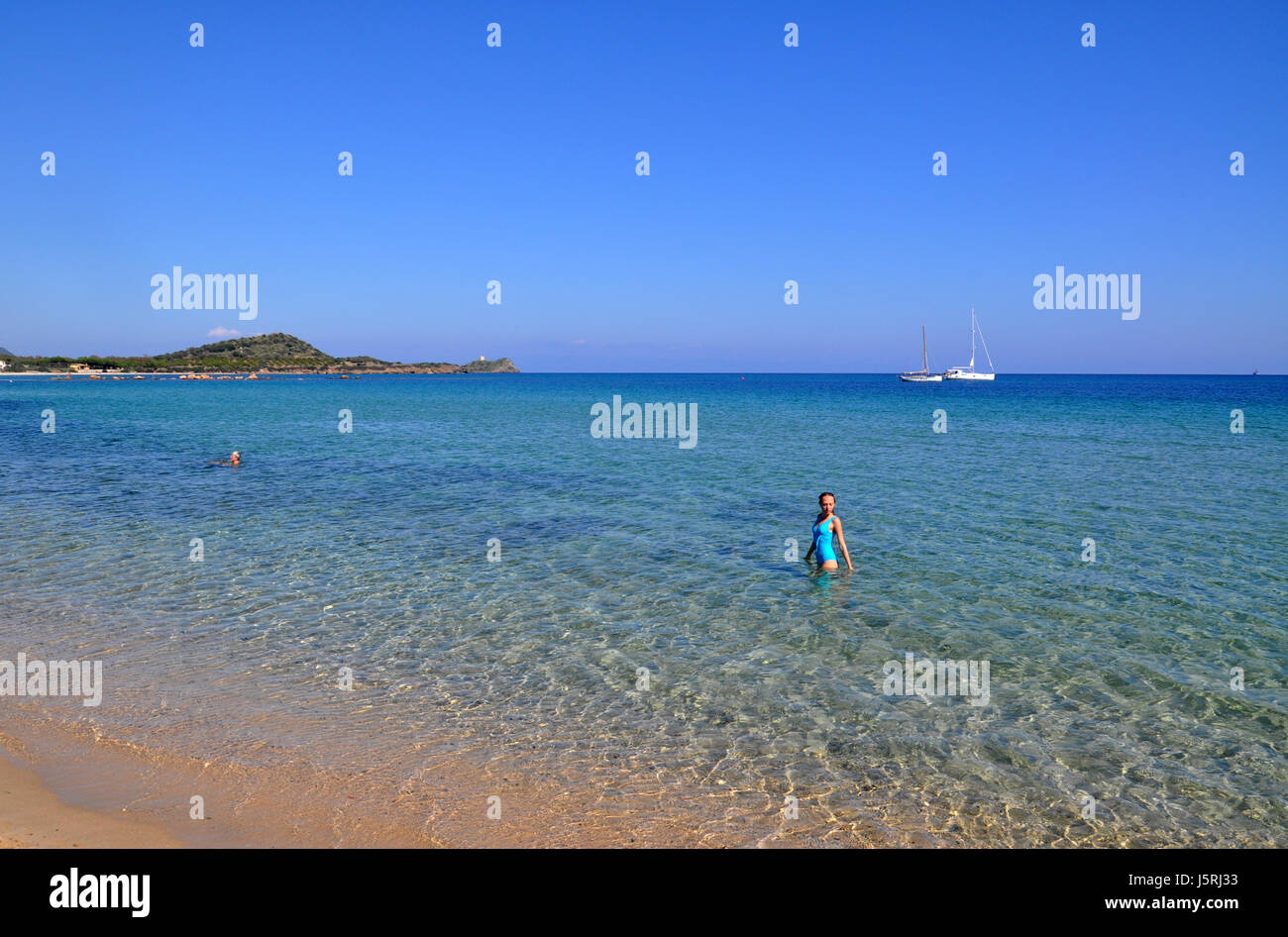 Young woman standing in transparent blue watersof the Mediterranean sea  with white sailing boats on Nora beach - Stock Image