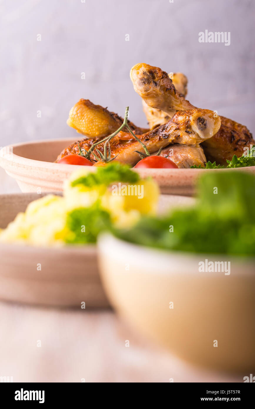 Vertical photo with baked or fried chicken legs on clay plate. Food is on wooden boarrd with grey textured background. - Stock Image