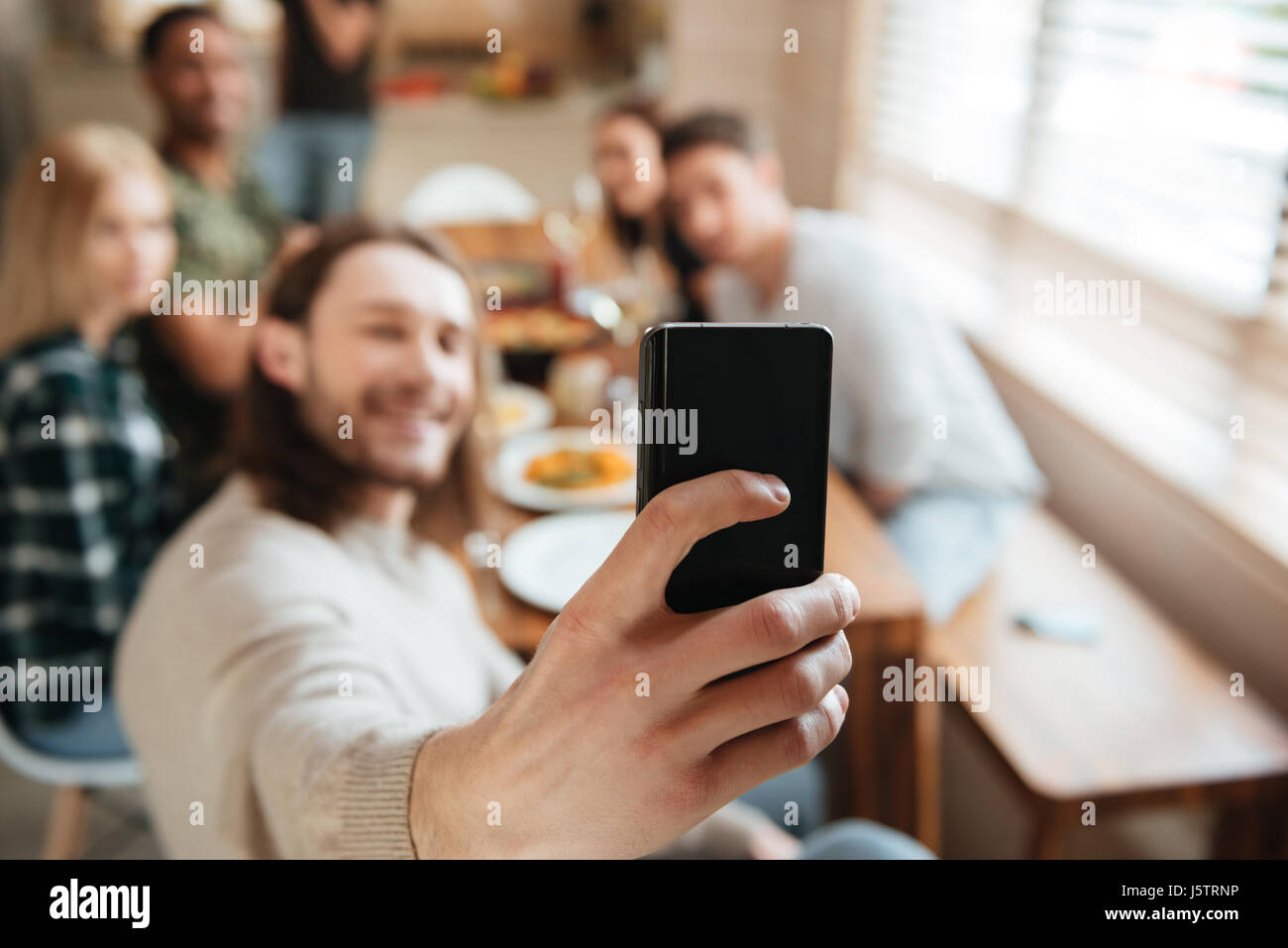Attractive young man taking a selfie photo with friends in the kitchen while having lunch together at home, focus - Stock Image