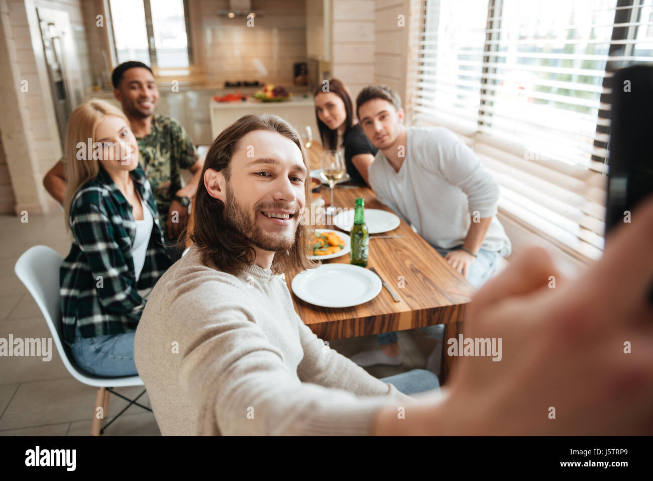 Attractive young man taking a selfie photo with friends in the kitchen while having lunch together at home - Stock Image