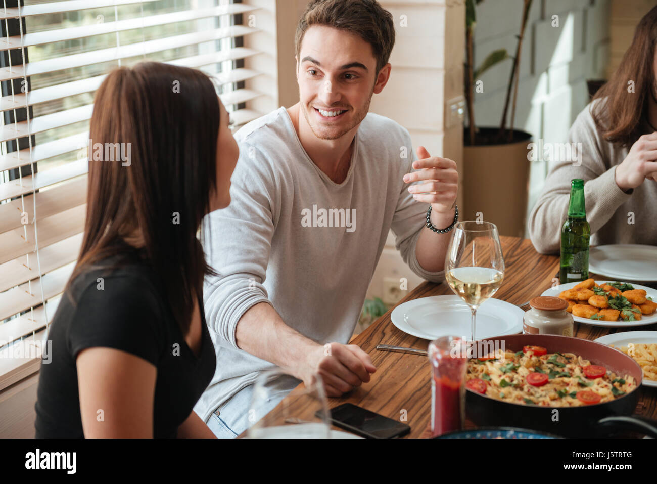 Happy young couple eating and talking at the table at home - Stock Image