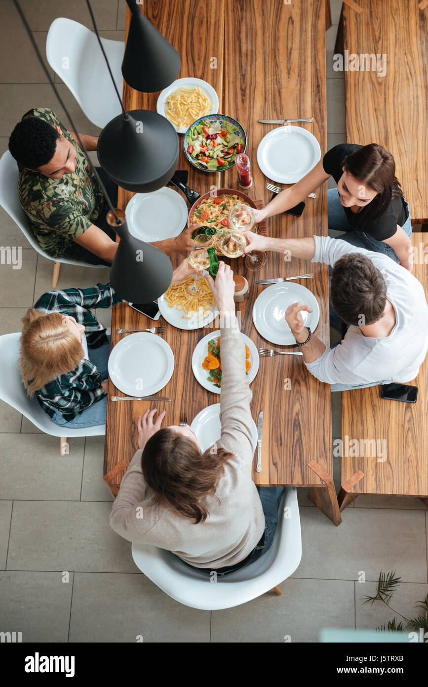 Top view of five people cheering with wine while sitting at the rustic dining table - Stock Image