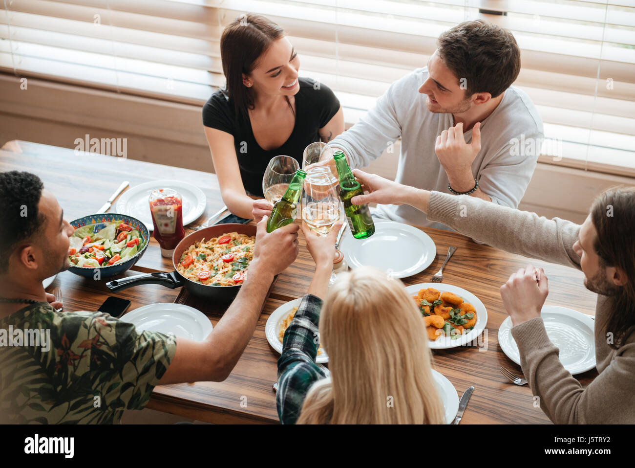 Top view of group of people clinking glasses and bottles at the table at home - Stock Image