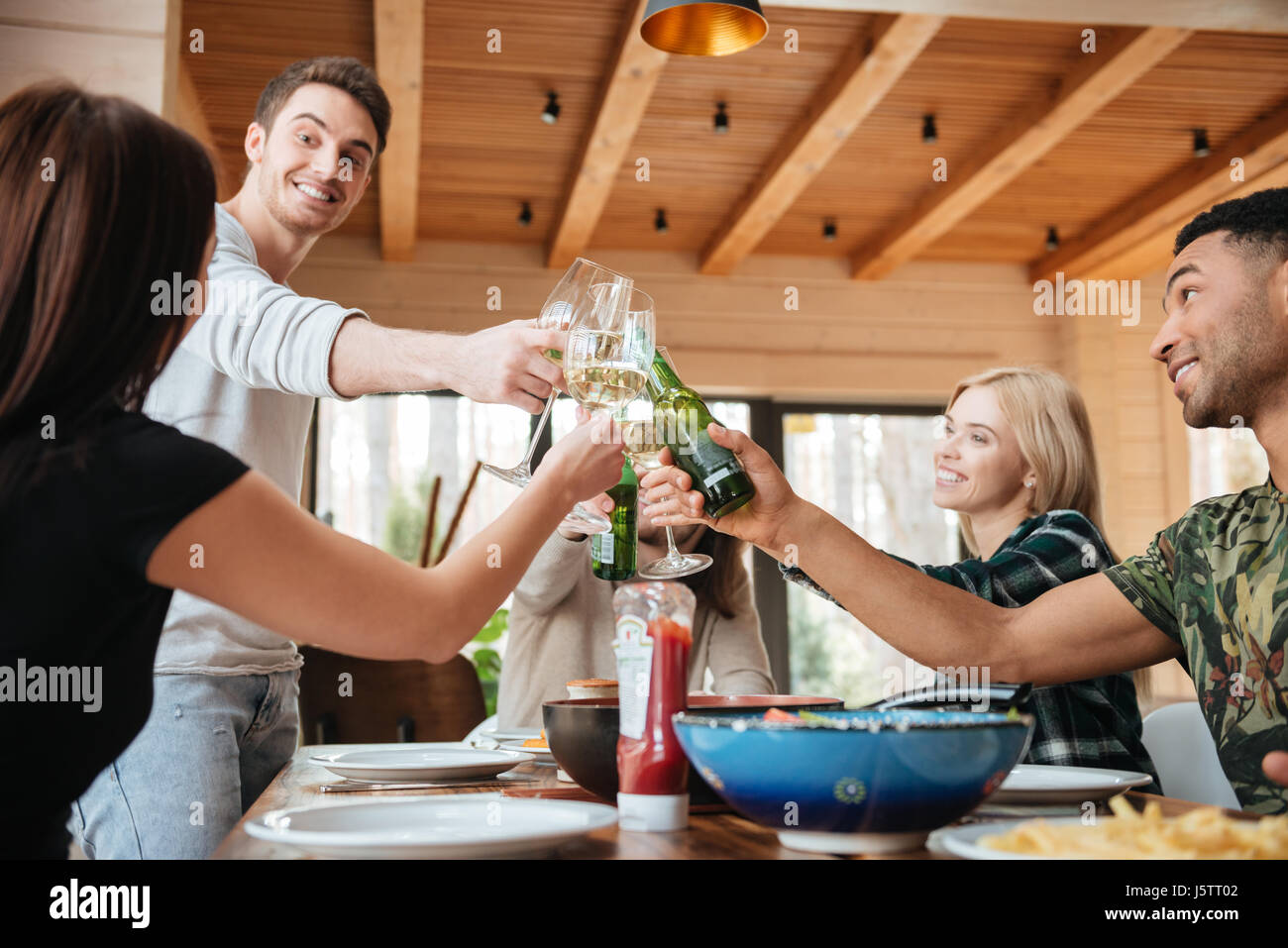 Multiethnic group of happy young people clinking glasses and celebrating at the table - Stock Image