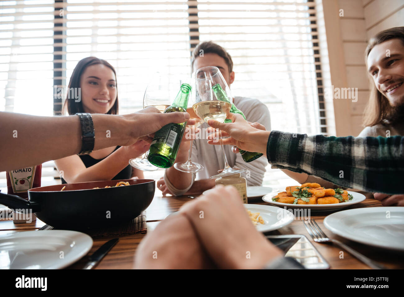 Side view of a group of young people saying cheers and eating healthy meals at party dinner table in cafe, restaurant - Stock Image