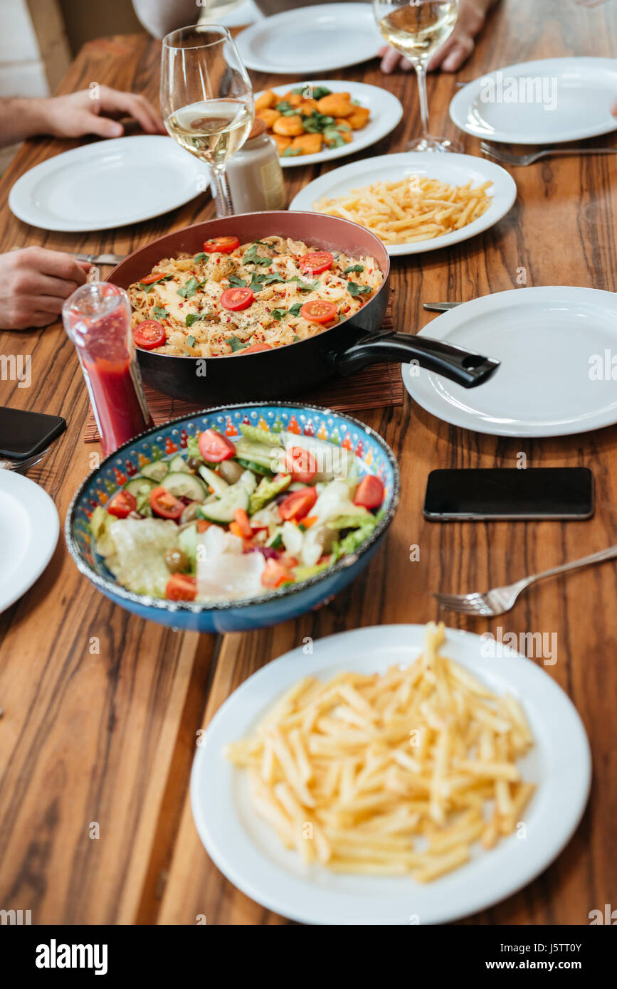 View on freshly prepared delicious varieties of home made dishes on wooden table - Stock Image