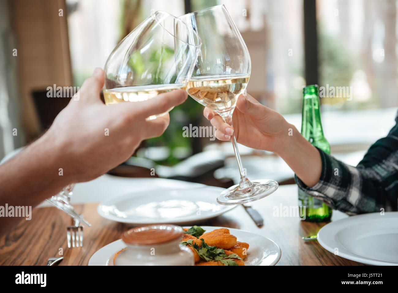 Close up portrait of a female and male hands toasting with glasses of white wine over table - Stock Image