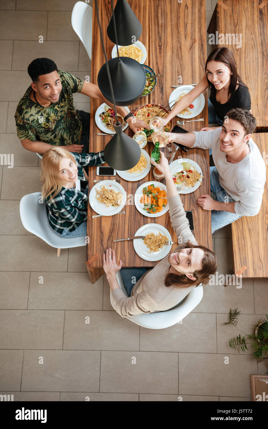 Top view of five people cheering with wine while sitting at the rustic dining table and looking up at camera Stock Photo