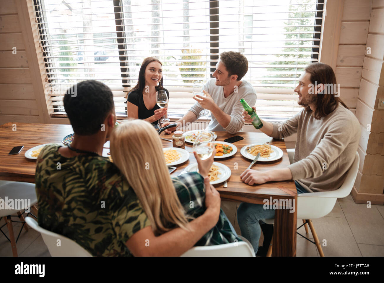Group of smiling young people having dinner and talking on the kitchen at home - Stock Image
