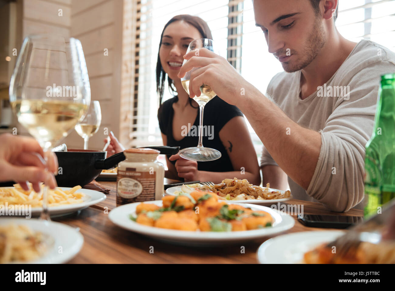 Beautiful young couple eating and drinking wine with friends on the kitchen at home - Stock Image