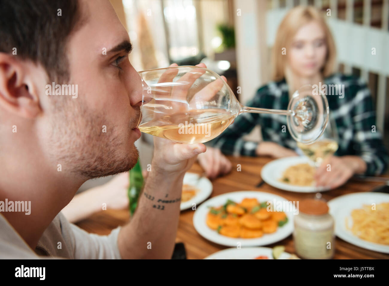 Closeup of handsome young man having dinner and drinking wine with friends on the kitchen - Stock Image