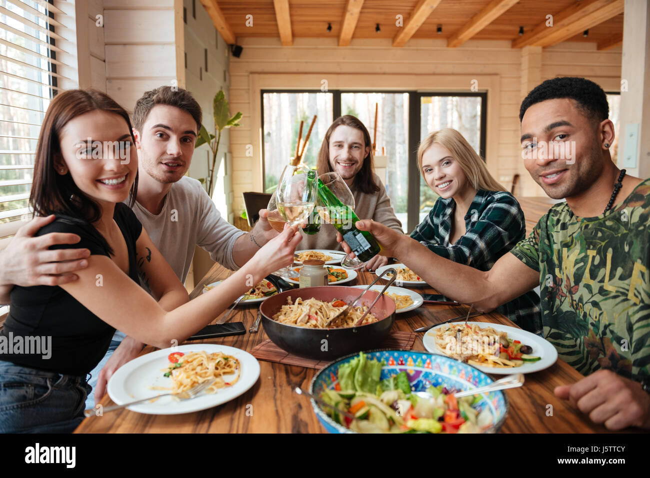 Group of happy young friends drinking wine and clinking glasses on the kitchen - Stock Image