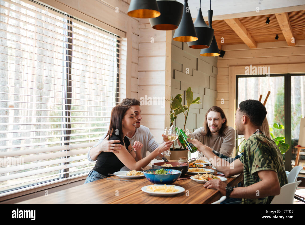 Group of cheerful young friends giving toasts and clinking glasses on the kitchen - Stock Image