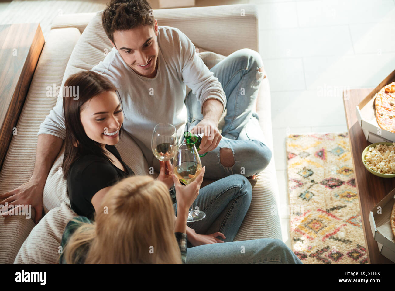 Top view of happy young friends clinking giving toasts and clinking glasses on sofa at home - Stock Image