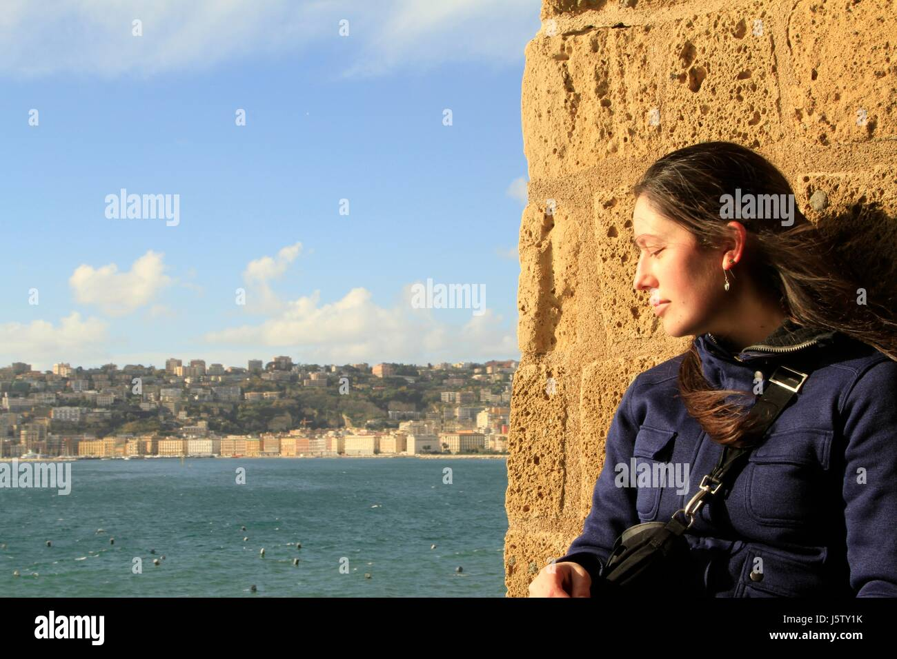Taking a moment at the Castel dell'Ovo overlooking the Gulf of Naples, Campania, Italy - Stock Image