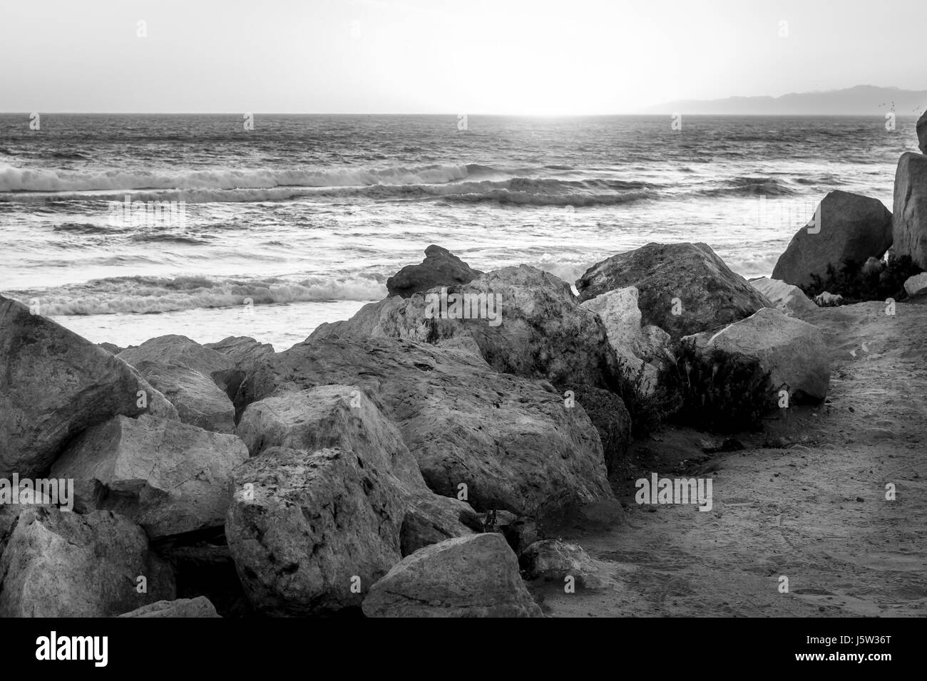 Black and white photo of a rocky seashore at sunset. - Stock Image