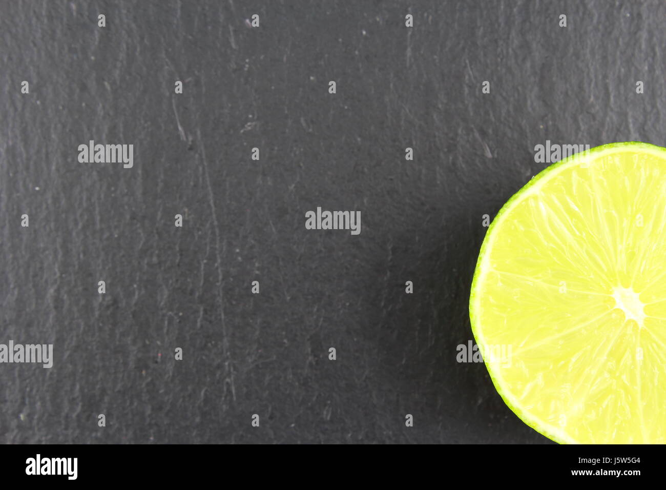 fresh lime fruit on a slate plate as a food background texture Stock Photo