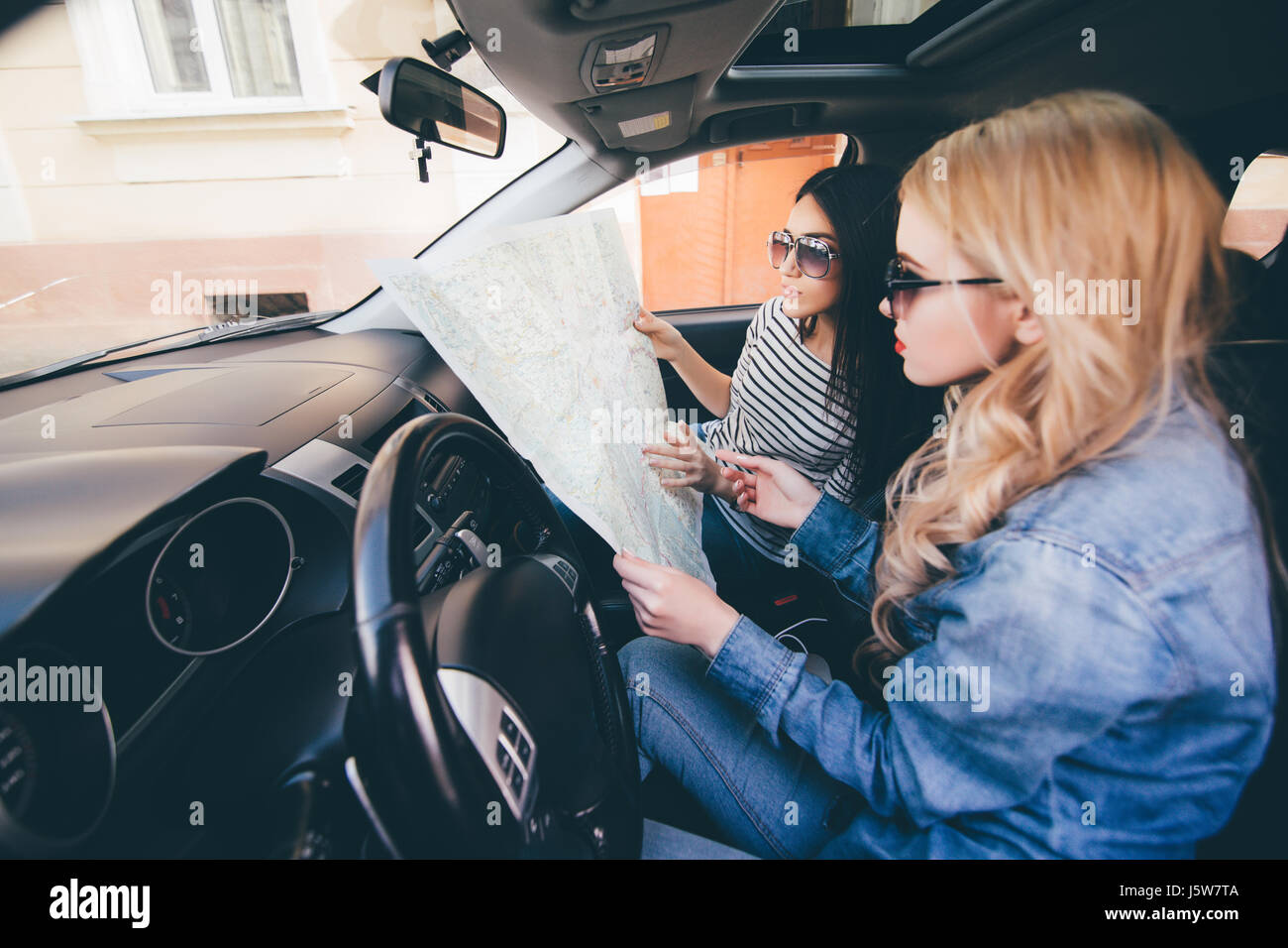 Women looking at map for directions while driving in car ... on car road map, car map parts, car world bugatti veyron, car services, car history, car trip, car driving map,