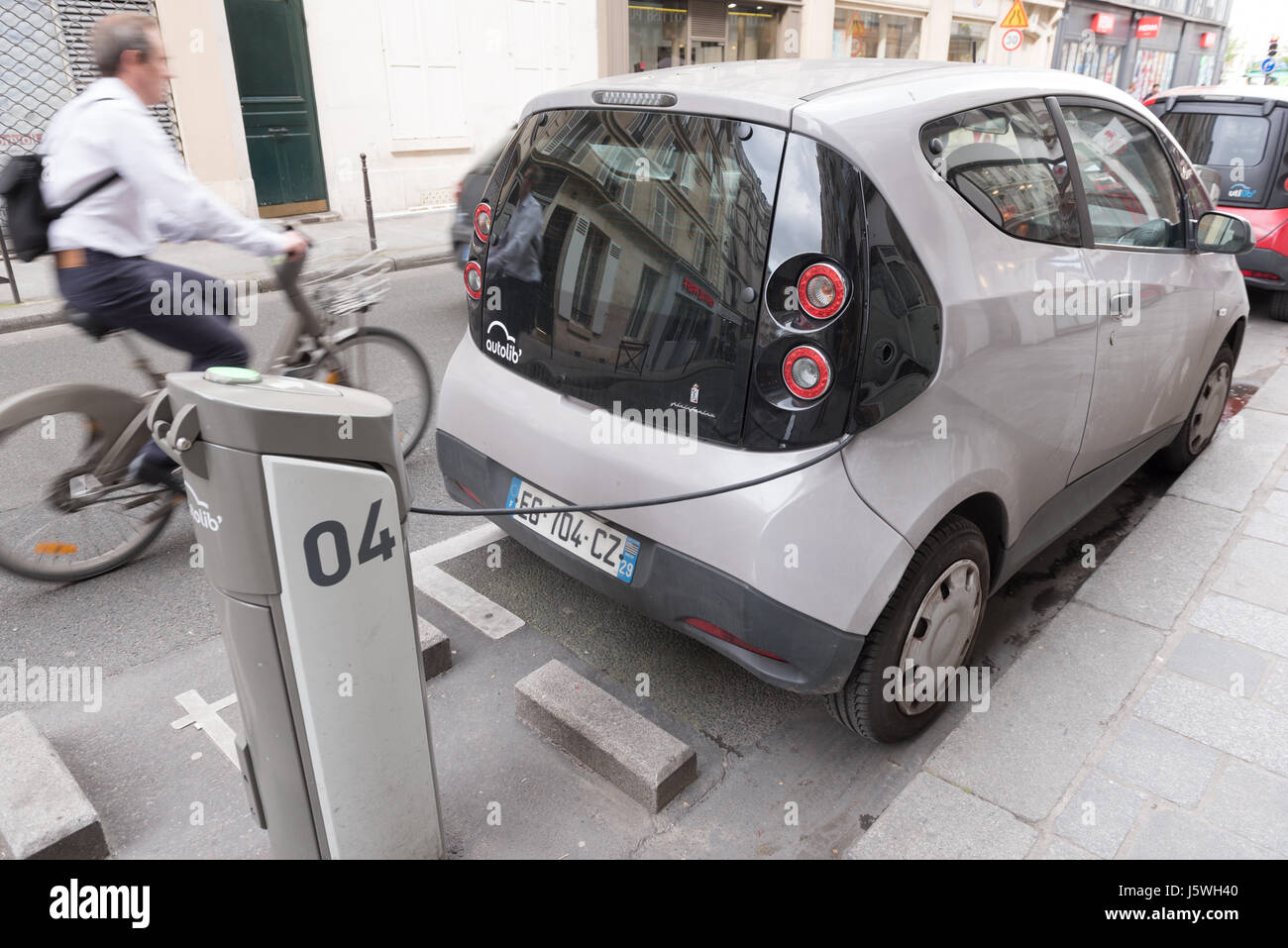 Paris, France 13th May 2017: Autolib car charging in a street of Paris with a blurry bike - Stock Image