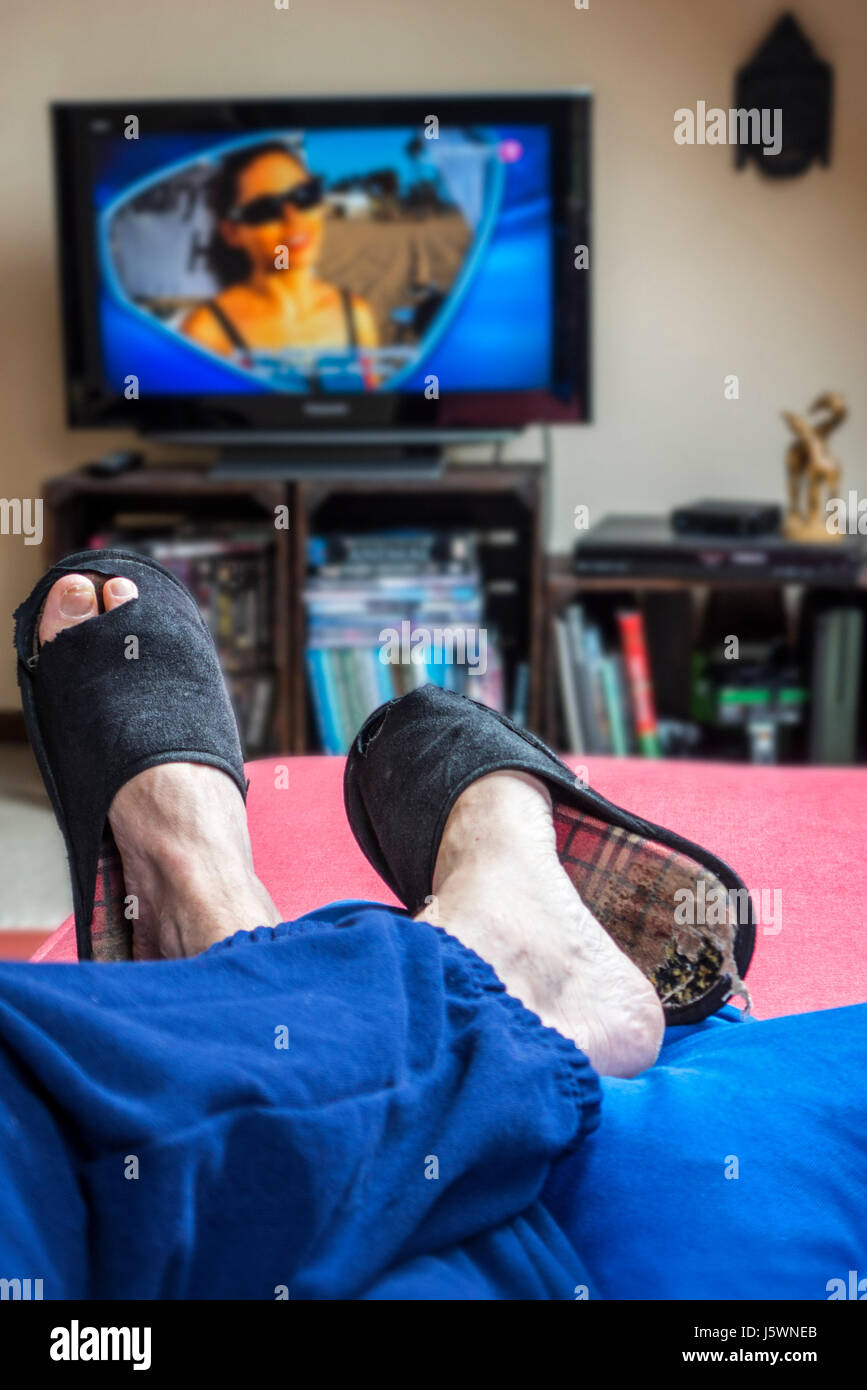 Couch potato, lazy man in comfy chair wearing worn slippers with big toes sticking through and watching television - Stock Image