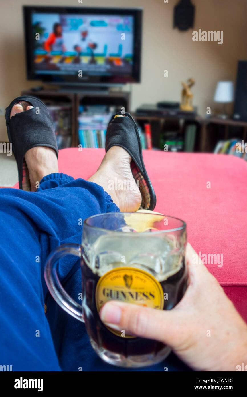 Couch potato, lazy man in comfy chair with pint of beer wearing worn slippers with big toes sticking through and - Stock Image