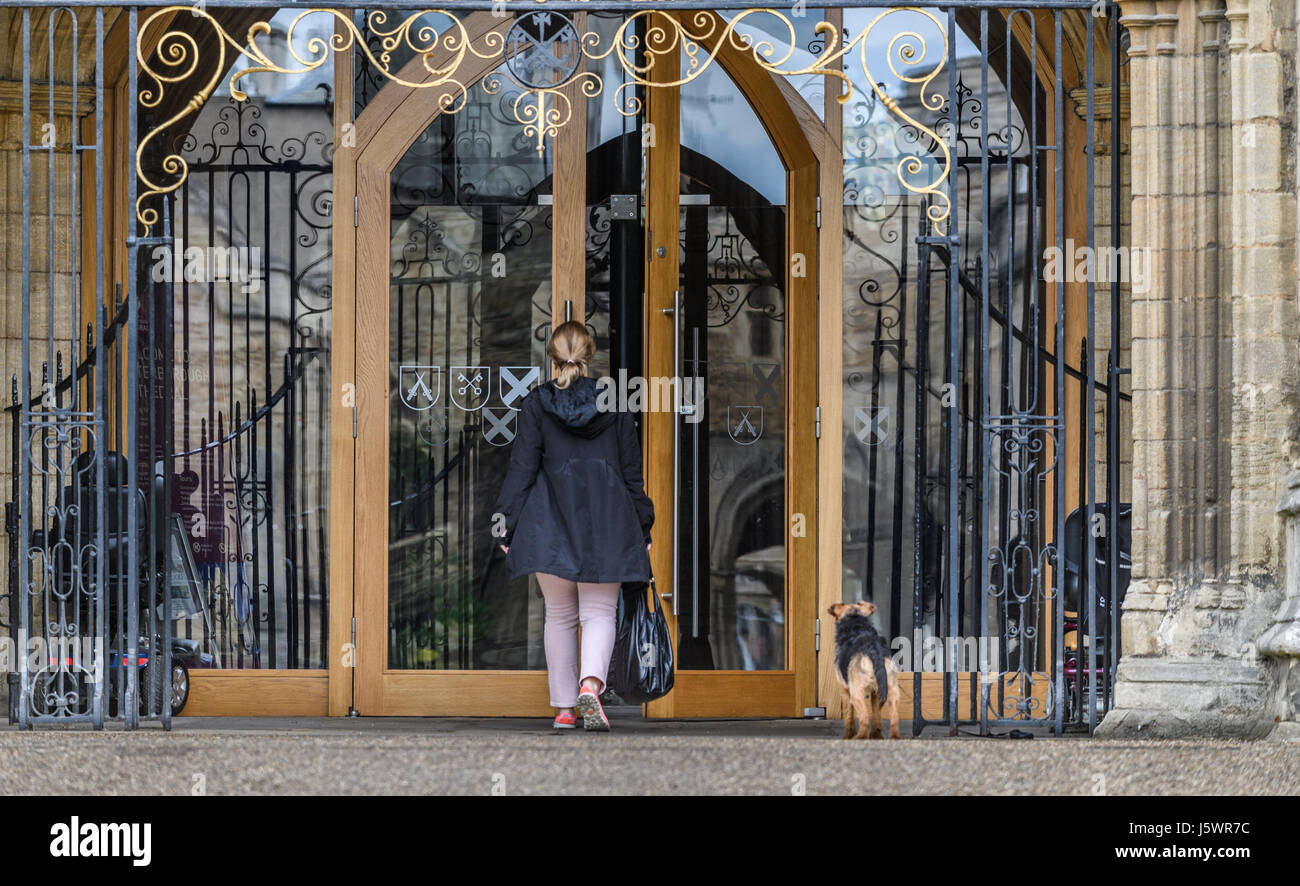 A visitor and a dog at the main door at the west facade of the medieval christian cathedral at Peterborough, England. Stock Photo