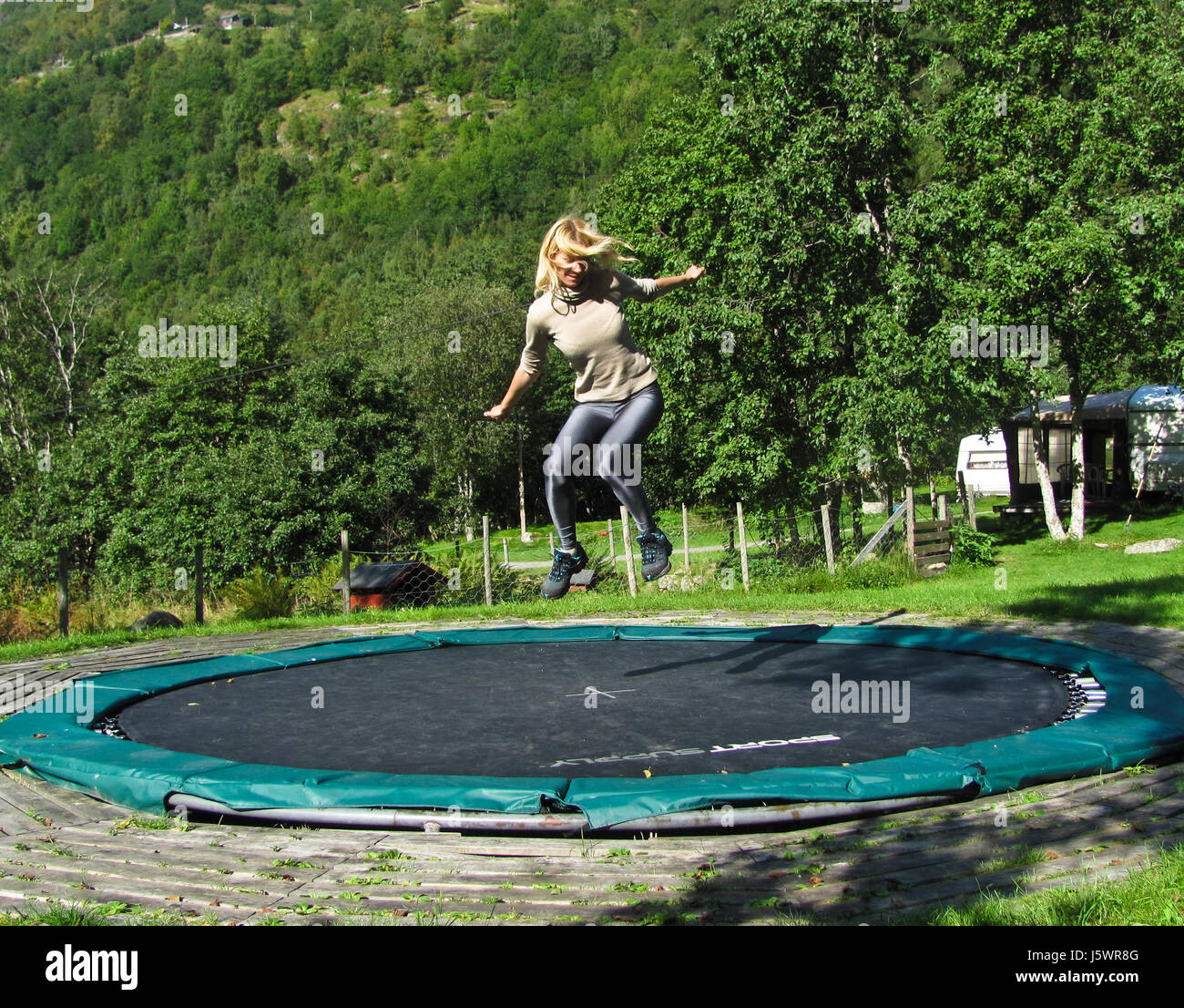 Girl jumping on a trampoline - Stock Image