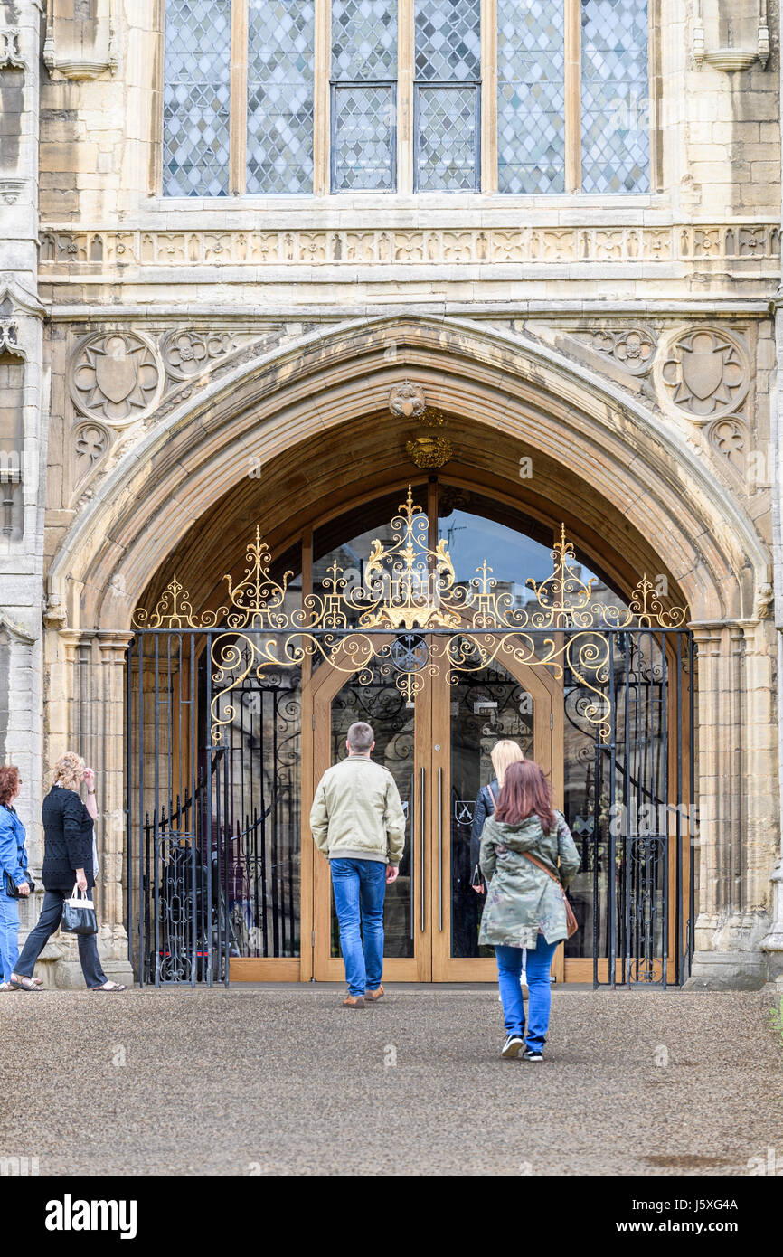 Visitors enter the main door at the west facade of the medieval christian cathedral at Peterborough, England. Stock Photo