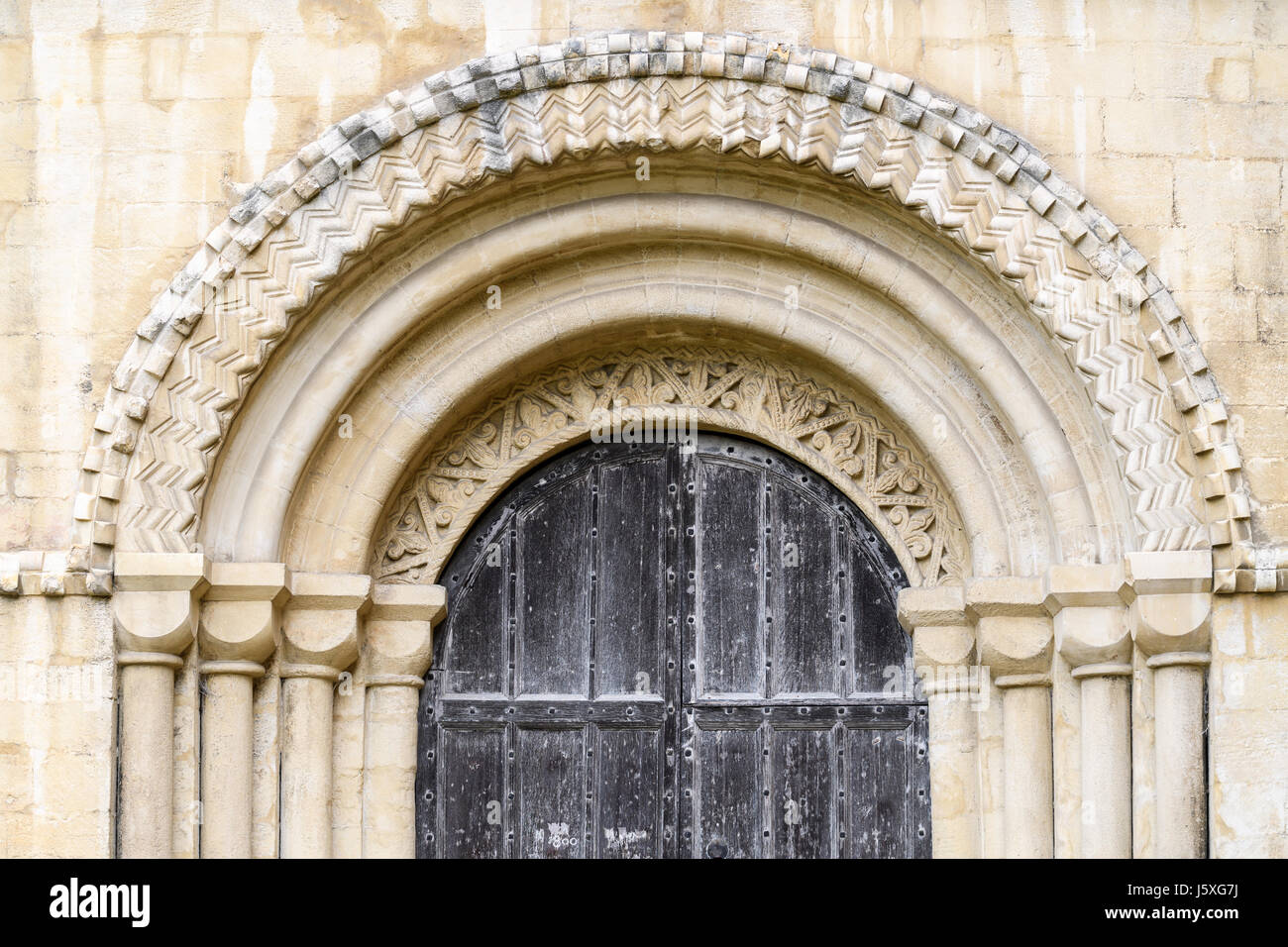 Intricate stone arch above a door on the south side of the medieval christian cathedral at Peterborough, England. Stock Photo