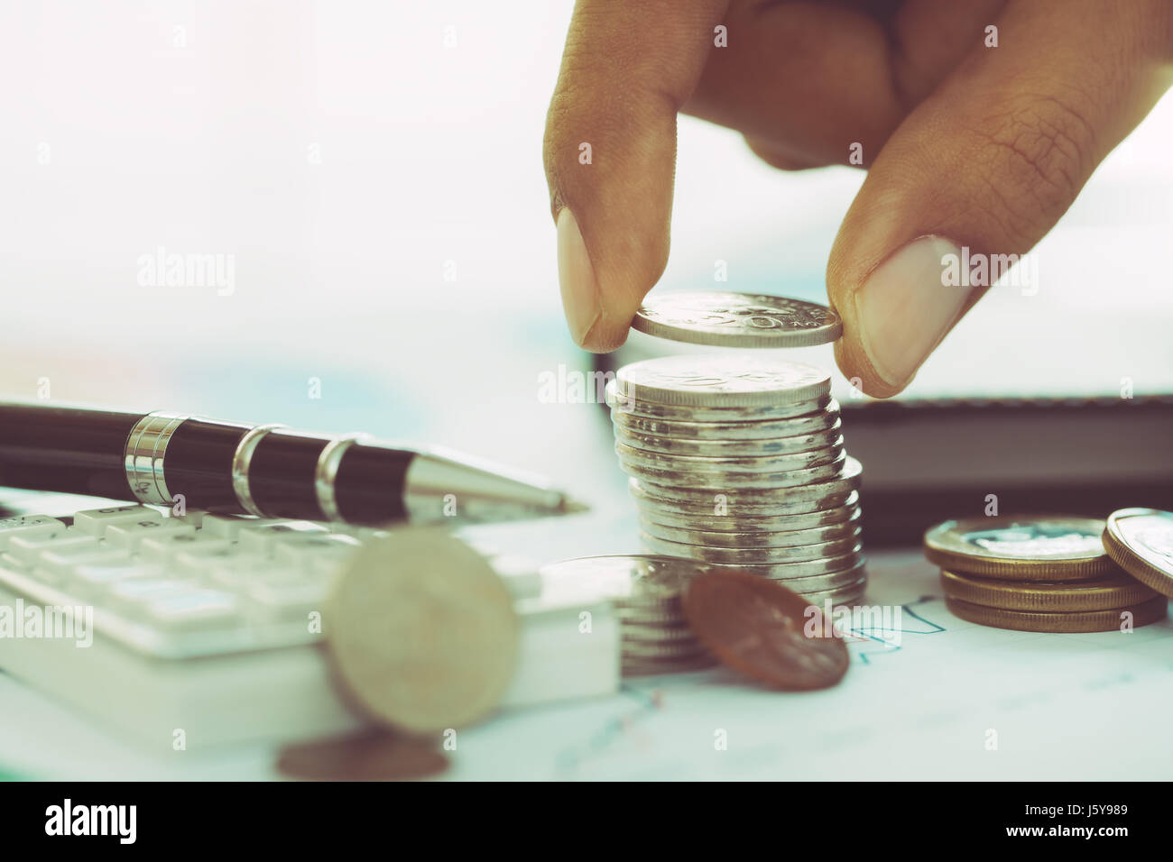 Hand putting coin on stack of coins with calculator and pen - Stock Image