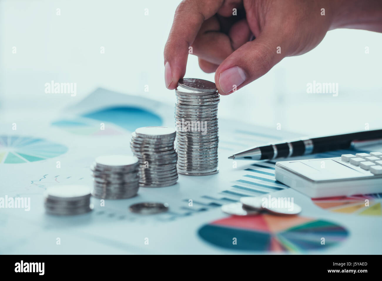 Business concept of saving money with coins and graph - Stock Image