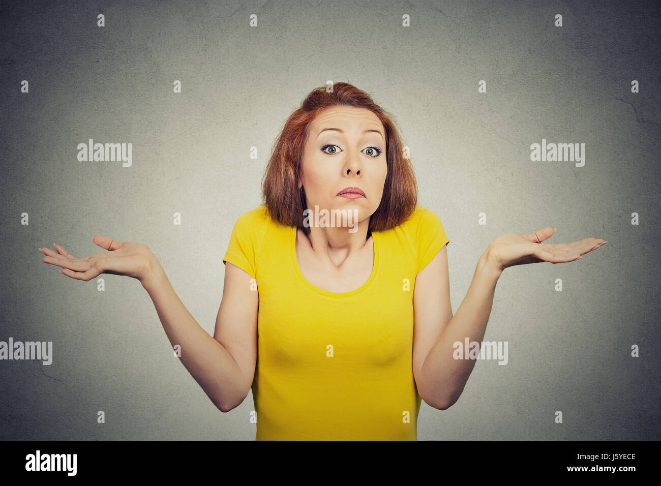 Closeup portrait puzzled clueless young woman with arms out asking what is problem who cares so what I don't - Stock Image