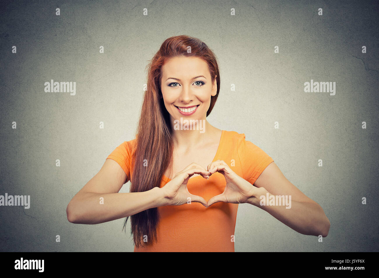 Closeup portrait smiling cheerful happy young woman making heart sign with hands isolated grey wall background. - Stock Image