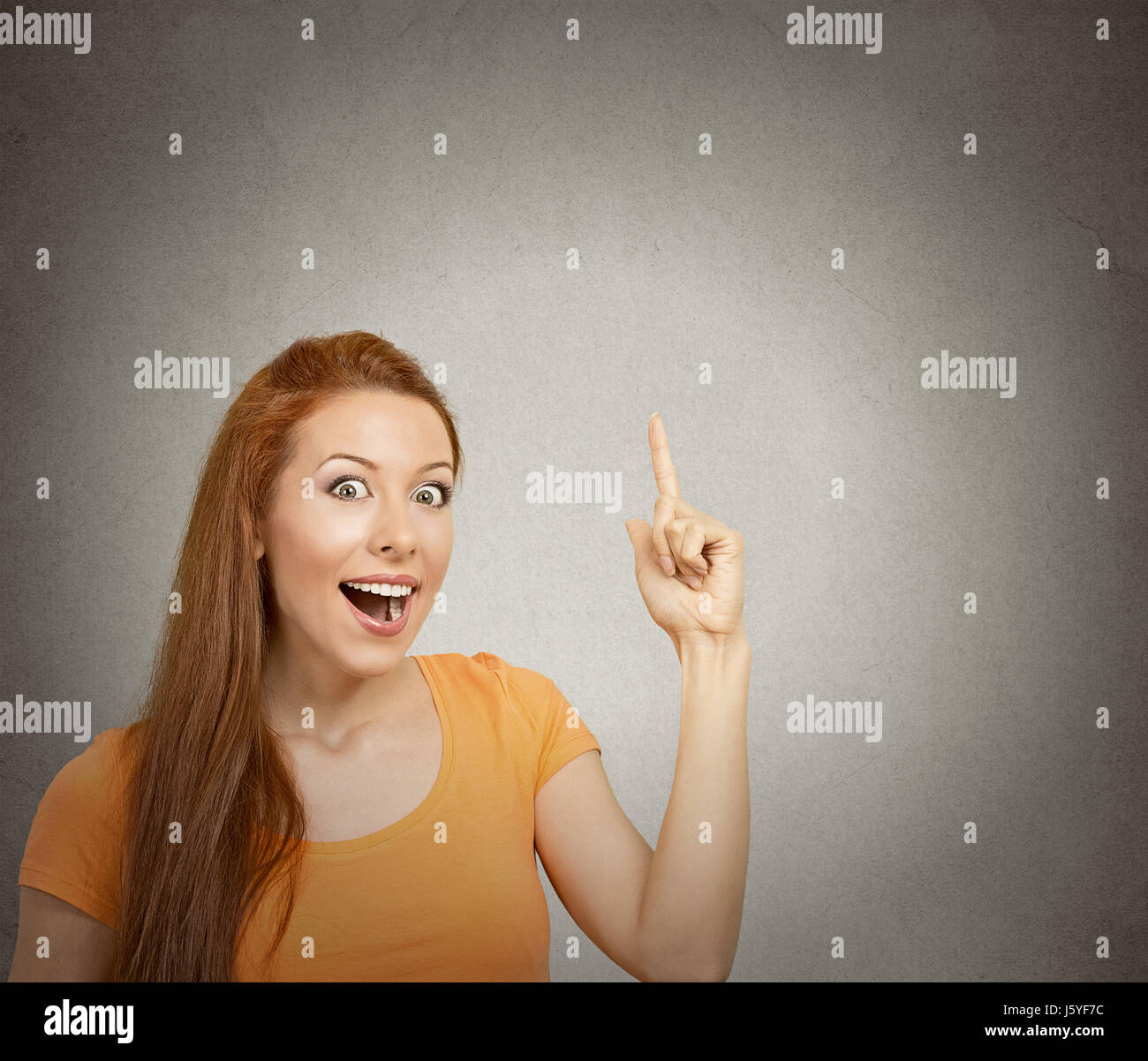 Closeup portrait intelligent excited young woman who just came up with idea aha isolated grey wall background with - Stock Image