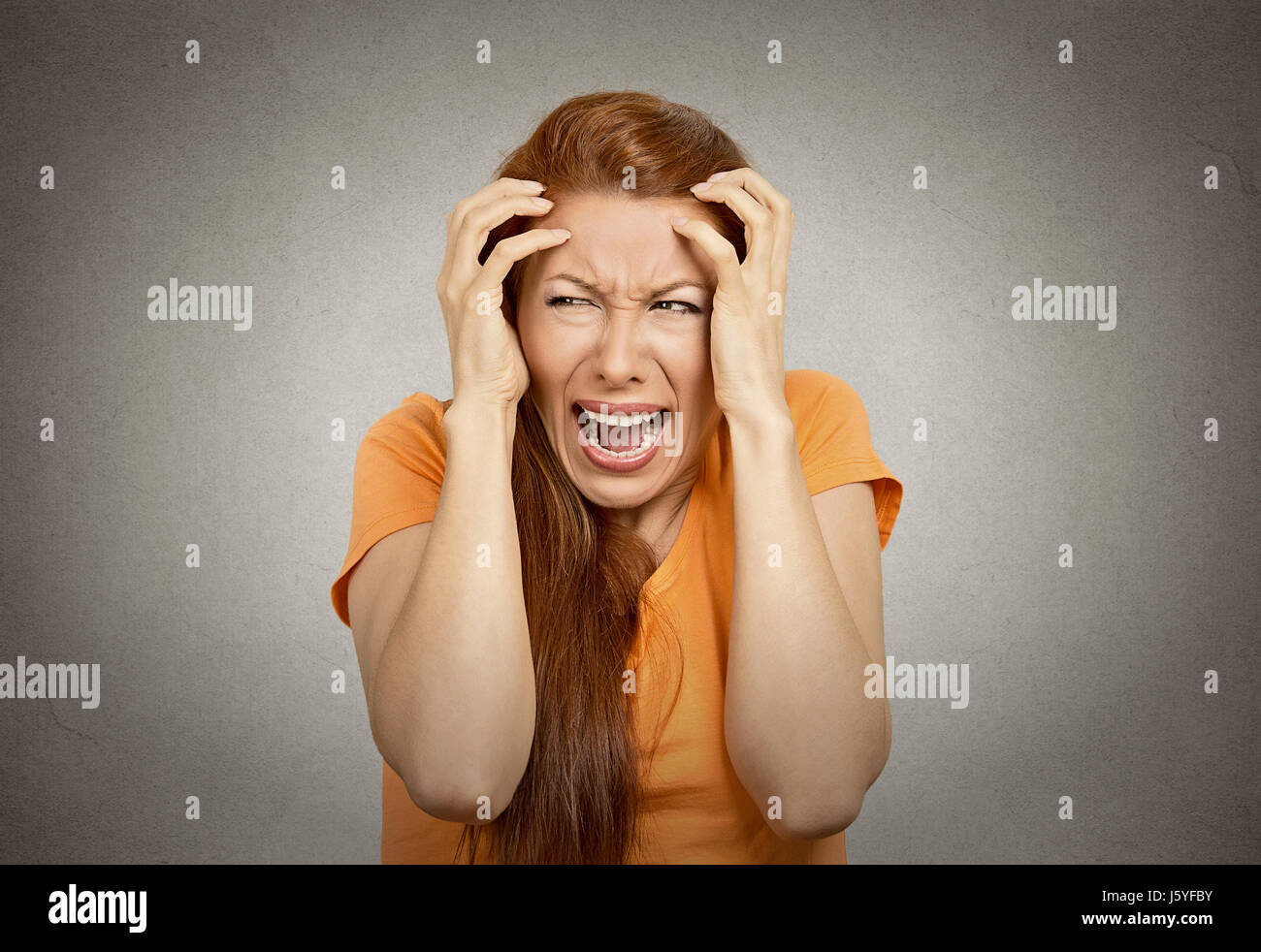 Closeup portrait stressed upset woman having breakdown hysterical yelling screaming temper tantrum isolated orange - Stock Image