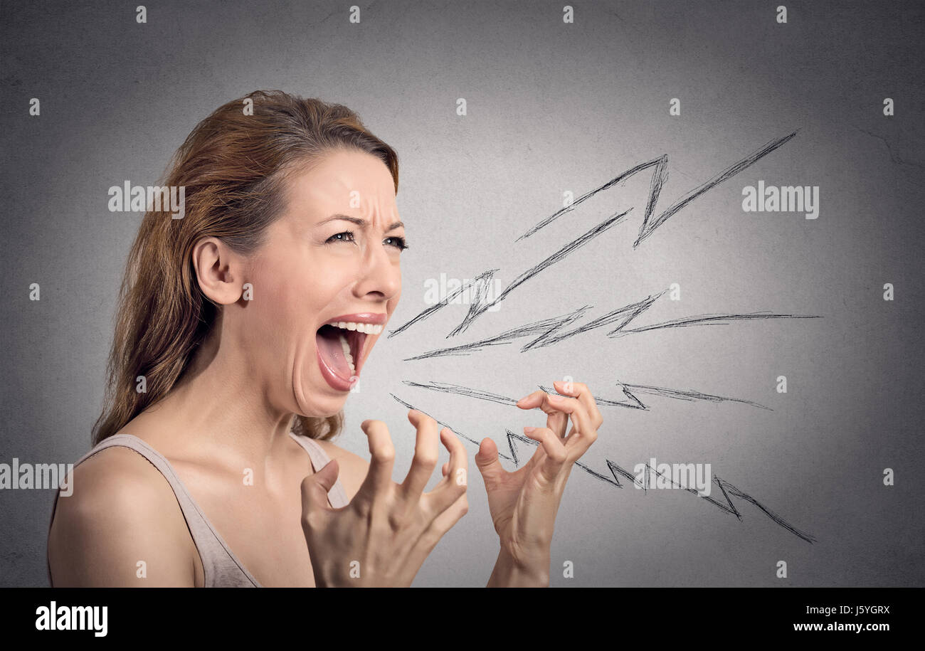 Side view portrait angry woman screaming, wide open mouth, hysterical isolated grey wall background. Negative human - Stock Image