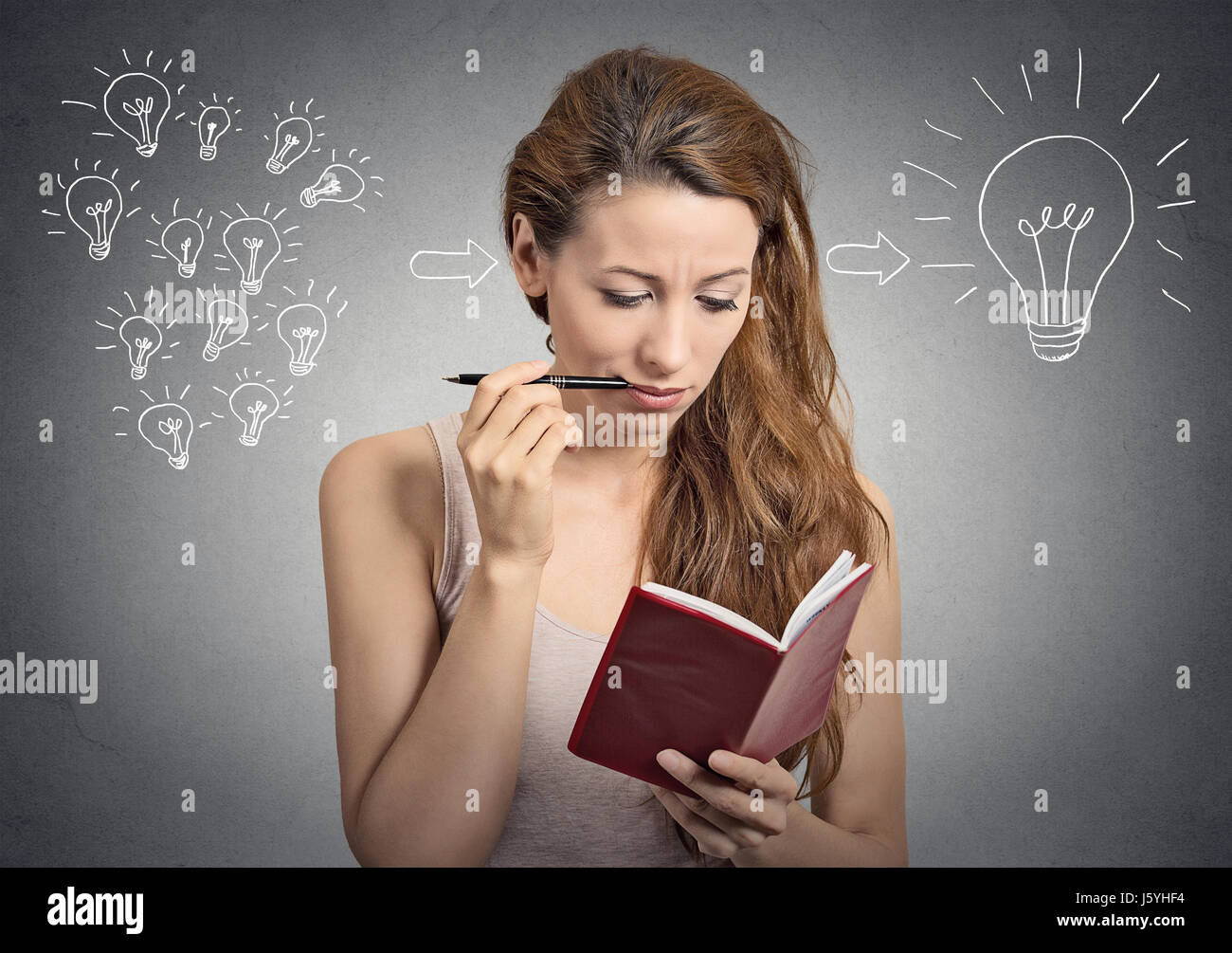 portrait beautiful girl thinking planning writing down notes isolated on grey wall background - Stock Image