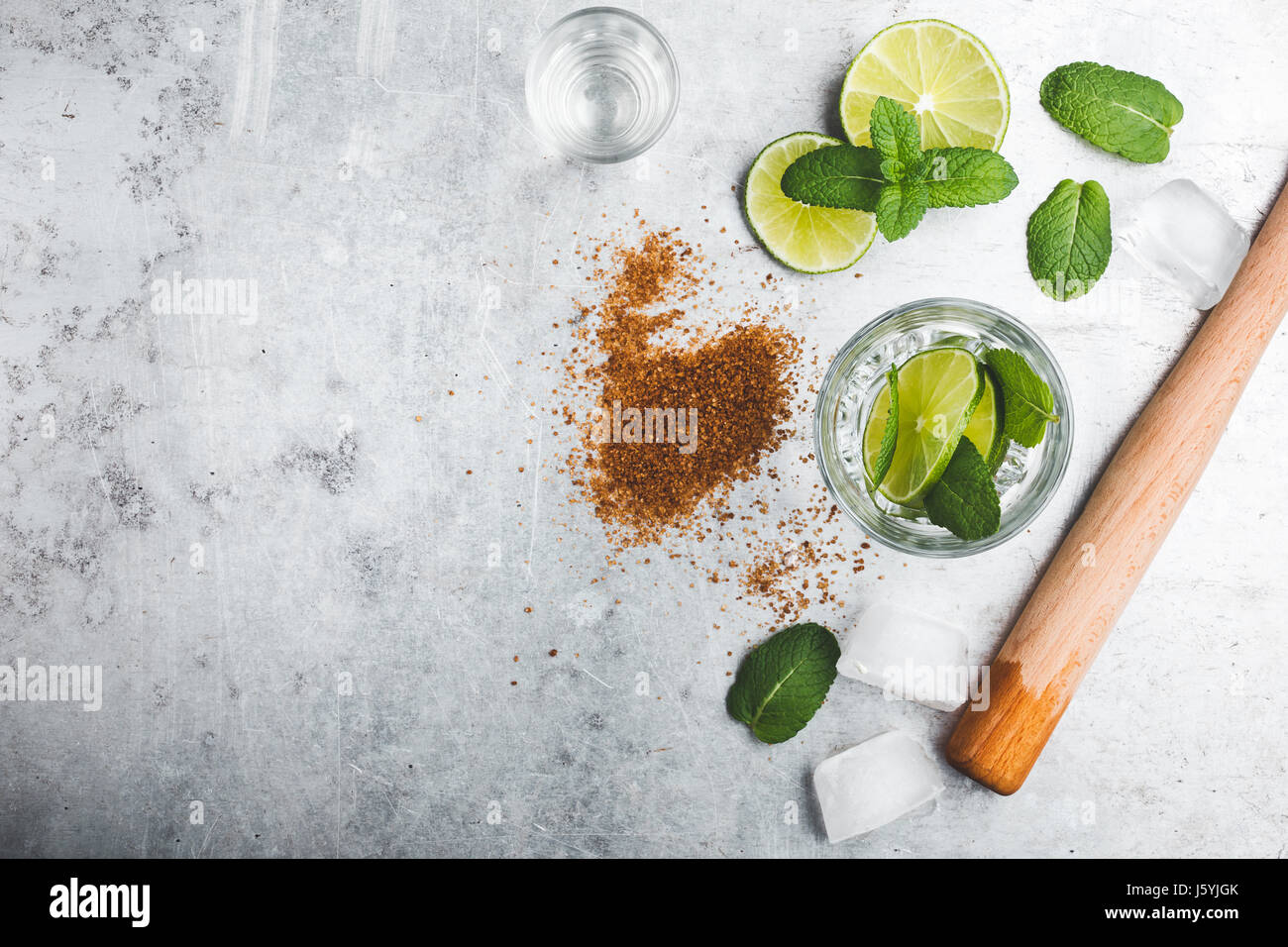 Mojito cocktail ingredients on light gray background. Lime slices, brown sugar, wooden squeezer, rum and mint leaves - Stock Image