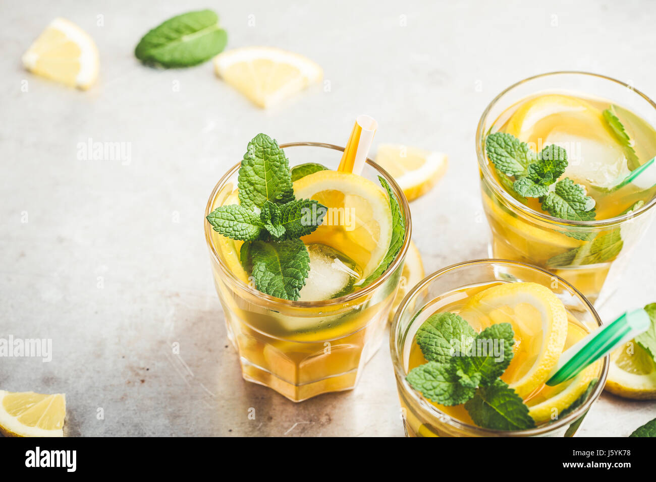 Homemade iced lemon sweet tea with mint on light gray table, delicious refreshment summer drink Stock Photo