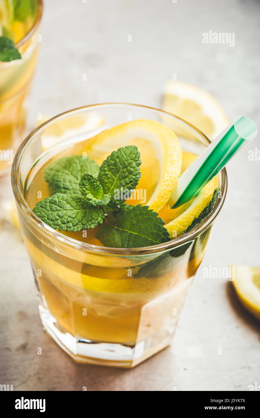 Homemade iced lemon sweet tea with mint on light gray table, delicious refreshment summer drink - Stock Image