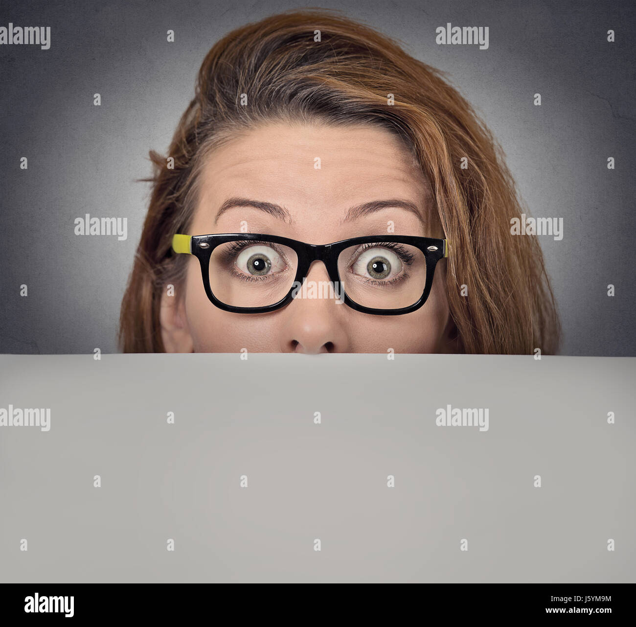 Banner sign woman peeking over edge of blank empty paper billboard. Beautiful young woman with glasses looking surprised - Stock Image