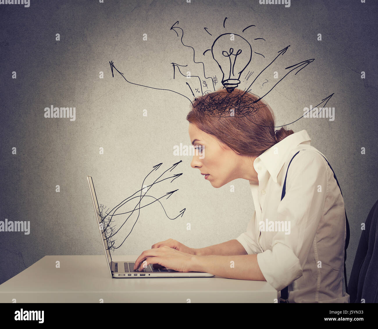 Young business woman working typing on computer in her office - Stock Image