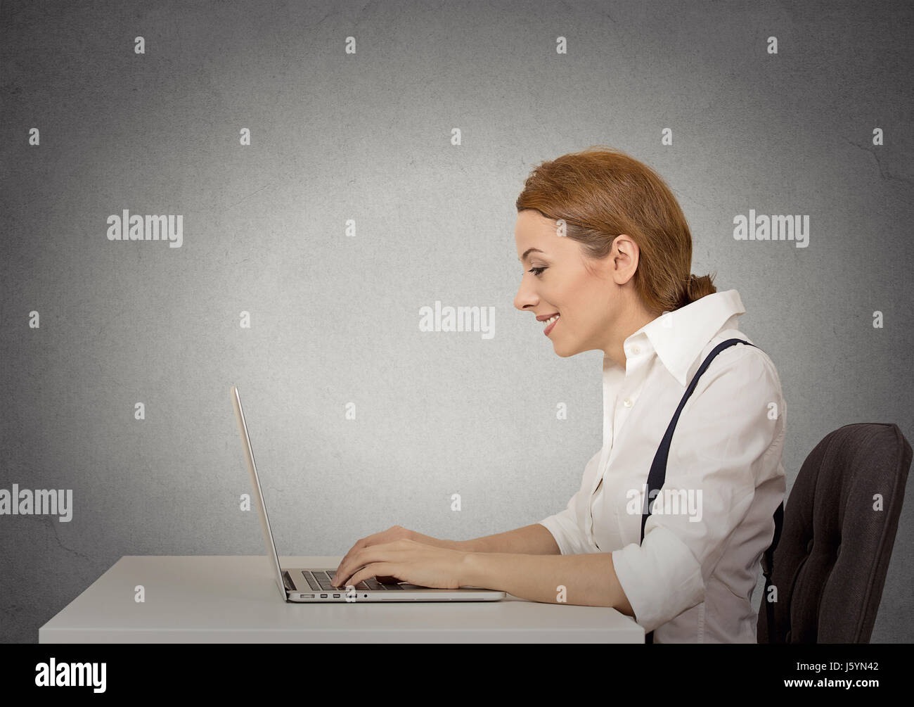 Side view profile attractive happy business woman using her laptop isolated grey wall background. Corporate executive - Stock Image