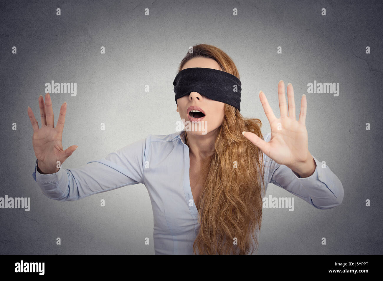 5cd7c49a8b9 Young businesswoman walking blindfolded with hands forward isolated on grey  wall background - Stock Image