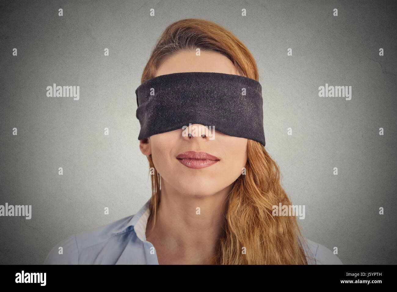 Blindfolded red haired woman - Stock Image