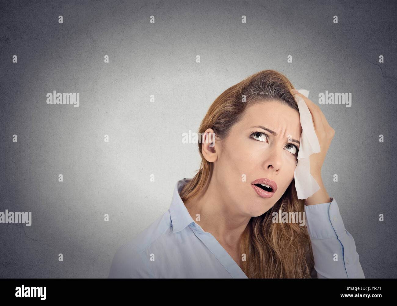 tired worried woman wipes sweat on her face - Stock Image